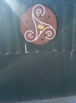 Triskelion with scallop shell on a door.